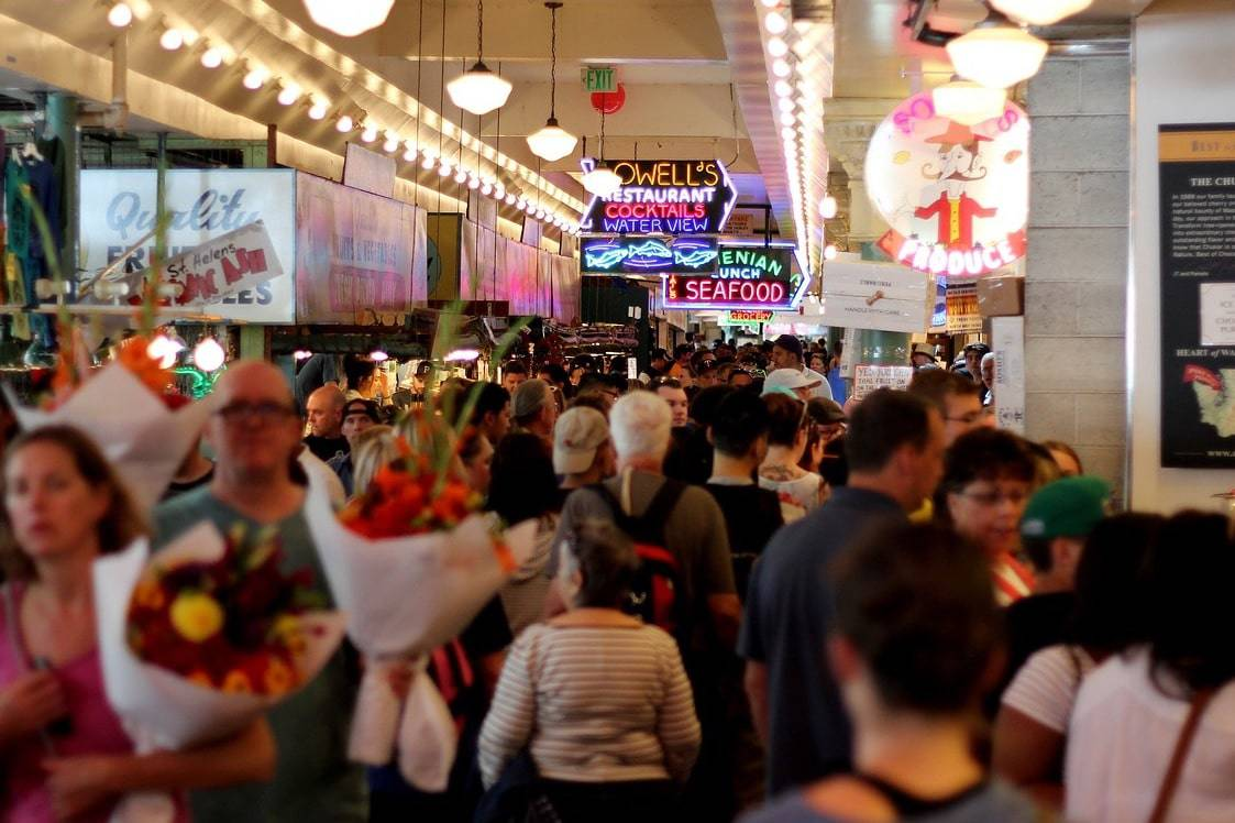 A crowd of shoppers in a gaudy mall shows the pathology of excessive consumption, which has a bad effect on the physical environment